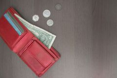 Low pay, lack of money. A red wallet with a dollar and credit cards, next to several coins. Hopelessness, a difficult financial situation, devotion, low incomes Royalty Free Stock Images