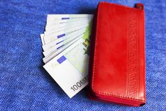 Red wallet with Euro banknotes,. On blue background Royalty Free Stock Images
