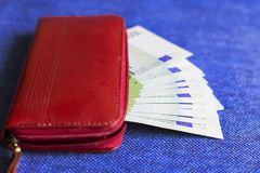 Red wallet with Euro banknotes,. On blue background Royalty Free Stock Photos