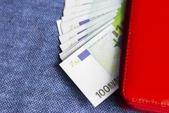 Red wallet with Euro banknotes. On blue background Stock Photos