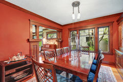 Red walls in dining room. Burgundy wooden table with carved chairs Stock Photography