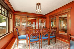 Red walls in dining room. Burgundy wooden table with carved chairs Stock Photos