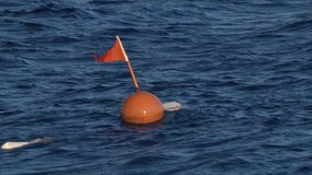 Red warning buoy is submerged in the water