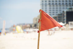 Red warning flag on the beach in Cancun, Mexico. A red warning flag on the beach in Cancun, Mexico warms swimmres that the waves are rough Stock Image