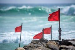 Red warning flag on beach Stock Photos