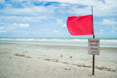 Red warning flag on the beach. A red flag and a sign warning people not to swim due to dangerous conditions Stock Photo