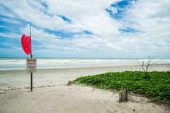 Red warning flag on the beach. A red flag and a sign warning people not to swim due to dangerous conditions Stock Photos