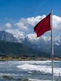 Red warning flag flying over Marinella beach, Apuan Alps, mountains behind. NOTE differential focus, focused on flag Royalty Free Stock Photos