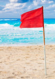 Red warning flag on a stormy beach Royalty Free Stock Photos