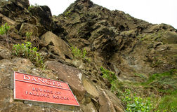 Red warning sign for falling rocks on a cliffs in Edinburgh, Sco Stock Photo