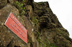 Red Warning Sign For Falling Rocks On A Cliffs In Edinburgh, Sco