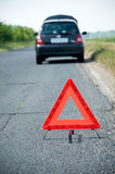Red Warning Triangle. Broken down car with red warning triangle stock photo