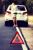 Red warning triangle and broken car in the middle of forrest stock photography