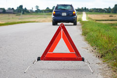 Red warning triangle and broken down car Stock Images