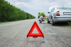 Red warning triangle with a broken down car. Breakdown of the car in bad weather stock photos