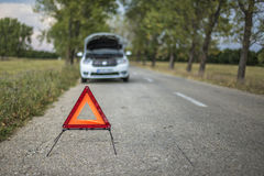 Red warning triangle with a broken down car Royalty Free Stock Photography