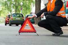 Red warning triangle with a broken down cars Stock Photography