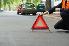 Red warning triangle with a broken down cars Royalty Free Stock Image