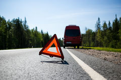 Red warning triangle with a broken down minibus Royalty Free Stock Photography