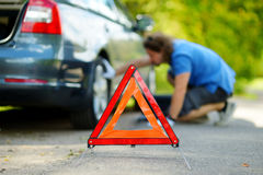 Red warning triangle sign on the road Royalty Free Stock Image