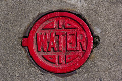 Red water cover. A red water cover in the ground is for the fire department to turn on or off the valve for the fire hydrant Royalty Free Stock Photo