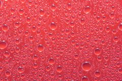 Red water droplets on a glass close up macro shot. Rainy days. royalty free stock photo