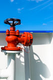 Red water or fuel valve against blue sky background. Stock Photos