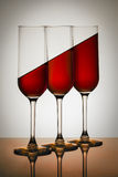 Red Water In Glasses. Glasses filled with red water on inclined plane Stock Photo