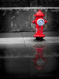 Red Water Hydrant. Detail of red water hydrant with puddle of water Stock Image