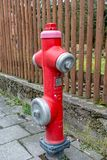 Red water hydrant in the middle of the footpath. A Red water hydrant in the middle of the footpath Stock Photo