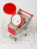 Red water meter in shopping cart. On draft background Stock Photos