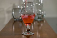 Red water poured into a glass in front of other glasses in background. Red ink swirling in water with other empty glasses behind on table royalty free stock images