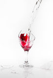 Red water spill from a broken wine glass on white background. Red water spill from a broken wine glass on a white background Royalty Free Stock Image
