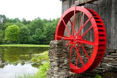 Red Water Wheel Mill Building and Pond Vermont. Idyllic mill pond and mill building.  An old mill powered by a bright red water wheel, and early example hydro Royalty Free Stock Photography