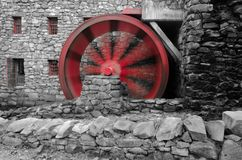 Red water wheel in motion at grist mill stock photography
