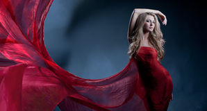 Red wave. Portrait of a gorgeous sexy blonde with long beautiful hair and body wrapped in red silk, like a flower Royalty Free Stock Image