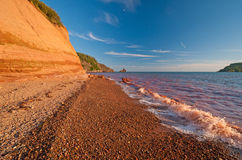 Red Waves on a Red Sandstone Beach Royalty Free Stock Images