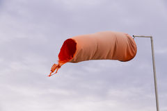 Red weathered windsock. Wind sock (or conical textile tube) red and worn at one end against a grey sky Stock Photo