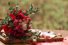 Red wedding bouquet with wedding decor. Red beautiful wedding bouquet with wedding decor on a table Stock Photos