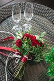 Red wedding bouquet on a glass table. two empty champagne glasses stock photography