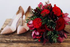 Red wedding bouquet. With peonies and women`s shoes on a wooden table on a happy wedding day royalty free stock images