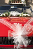 Red wedding car. With white ribbon and flowers on the windshield stock image
