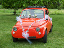Red wedding car. Italian red wedding car with white flowers Stock Photo