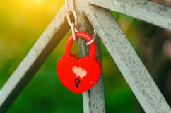 Red Wedding closed lock in the form of heart. The castle weighs in at a bridge on a blue sky background on a bright Sunny day. Stock Images