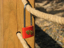 Red wedding lock with two golden hearts on protective rope of the bridge Royalty Free Stock Photo
