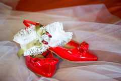 Red wedding shoes and garter belt. On white netting Stock Photos