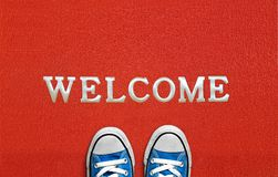 Red welcome carpet with blue sneakers on it. welcome sign concept.  royalty free stock photo
