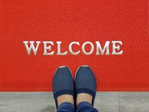 Red welcome carpet with foot-ware on it. Red welcome carpet on wooden floor with foot ware on it stock photography