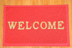 Red welcome carpet on wooden background Royalty Free Stock Photos