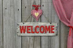 Red welcome sign hanging on wood background with gingham and gold hearts Royalty Free Stock Image